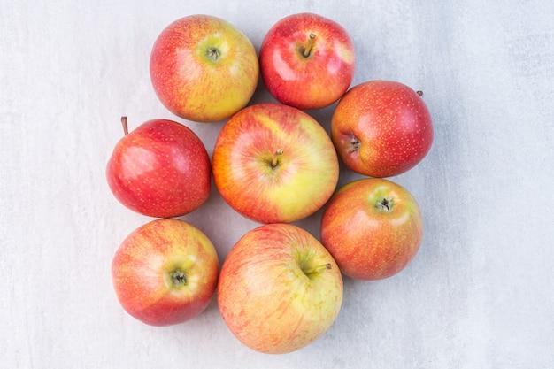 Ein haufen roter frischer äpfel auf dem marmor.