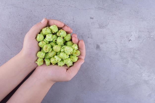 Ein haufen von aromatisiertem popcorn, der von zwei händen auf marmorhintergrund gehalten wird. foto in hoher qualität