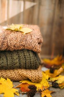 Ein haufen warmer pullover auf einem holztisch mit herbstlaub, strickwaren, platz für text, herbst-winter-konzept.