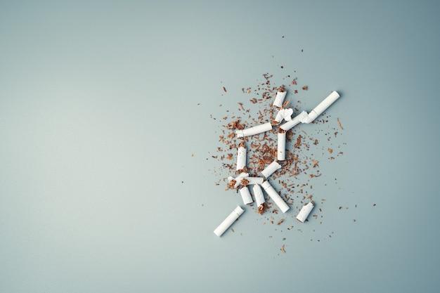 Ein haufen zerbrochener zigaretten und tabak auf grauem hintergrund.