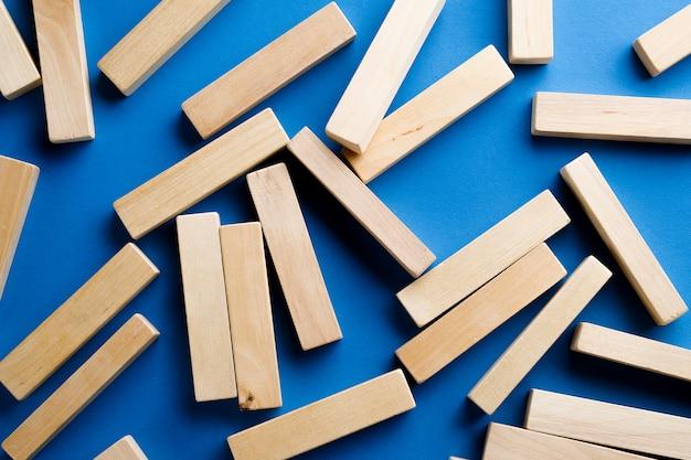 Ein haufen zerstreuter holzblöcke auf einem blauen hintergrund. konstruktionsspiel. der zerbrochene turm.