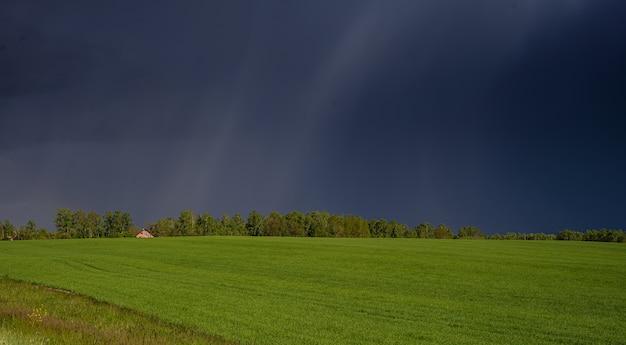 Ein haus inmitten einer grünen wiese und eines stürmischen himmels