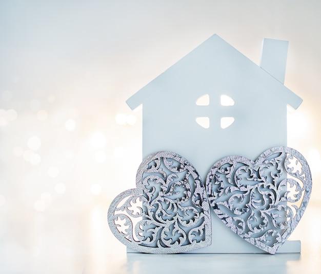 Ein hausmodell und graue herzen für familie auf hintergrund mit hellem bokeh. familien- und valentinstagskonzept.