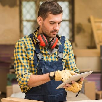 Ein heimwerker, der digitale tablette in der werkstatt verwendet