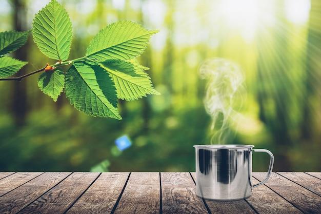 Ein heißer kaffee auf dem tisch auf einem frühlingshintergrund