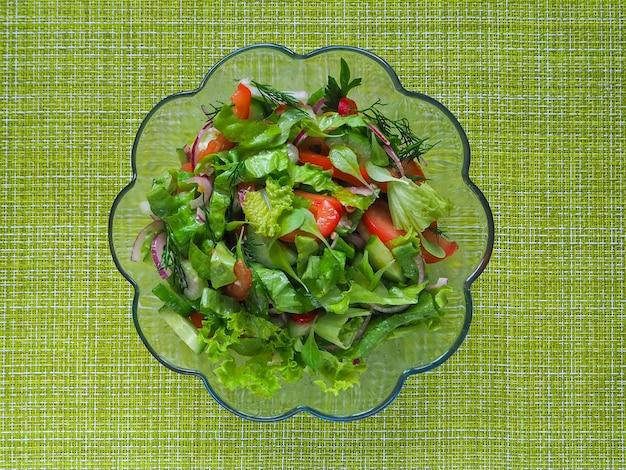 Ein heller gemüsesalat auf einem grünen hintergrund. sommer salat.