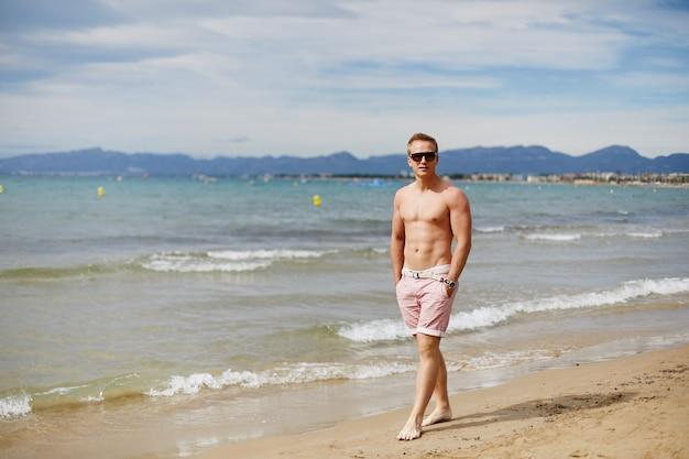Ein hemdloser muskulöser junger mann in strandshorts geht am strand spazieren. reisemode. sportlicher lebensstil.