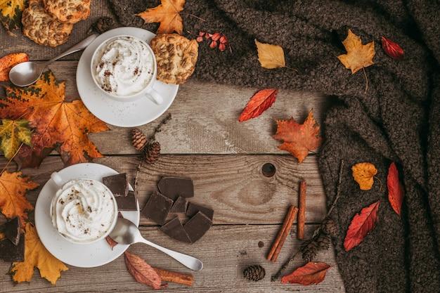 Ein herbstlicher tag, eine tasse leckeren kaffee auf einem hölzernen hintergrund. saison-, morgenkaffee-, sonntagsentspannungs- und stilllebenkonzept. mit textfreiraum.