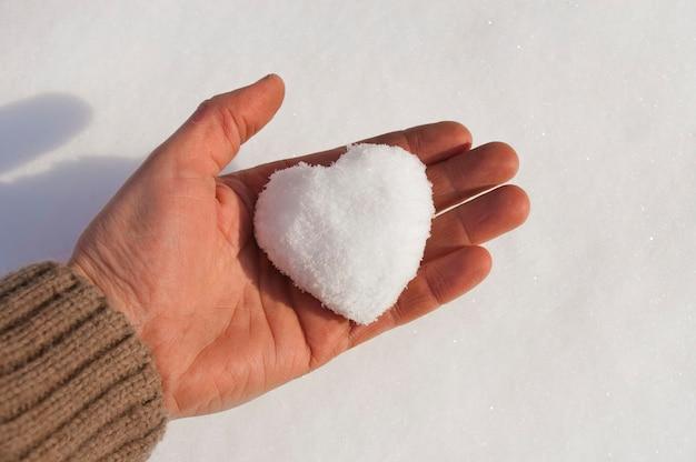 Ein herz aus schnee zur hand auf weißem schnee