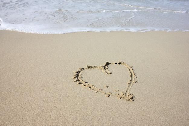Ein herz wird auf den sand des strandes gemalt