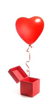 Ein herzförmiger ballon fliegt aus einer offenen geschenkbox. box und ballon lokalisiert auf weißem hintergrund. valentinstag geschenk. Premium Fotos