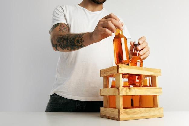 Ein hipster im einfachen weißen t-shirt, das flaschen der orange limonaden in eine holzkiste auf weißem tisch verpackt