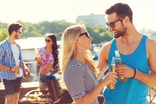 Ein hoch auf uns! lächelndes junges paar, das gläser mit bier anstößt und sich ansieht, während zwei leute im hintergrund grillen