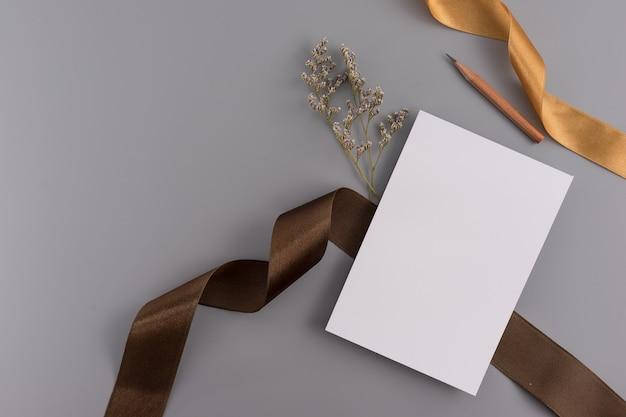 Ein hochzeitskonzept. hochzeitseinladungskarte auf grauem hintergrund mit band und dekoration.
