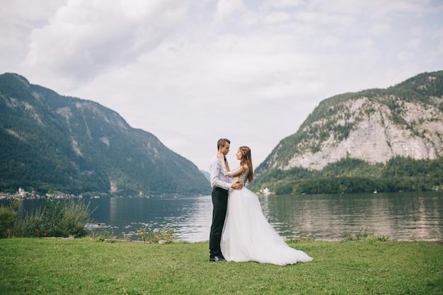 Ein hochzeitspaar auf dem hintergrundsee und den bergen in der märchenstadt von österreich
