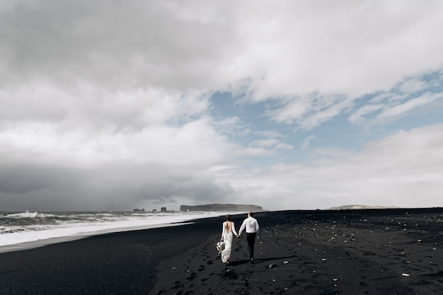 Ein hochzeitspaar geht entlang des schwarzen strandes von vic sandstrand mit schwarzem sand am ufer