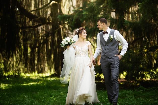 Ein hochzeitspaar geht gerne im wald spazieren. jungvermählten umarmen und halten die hände