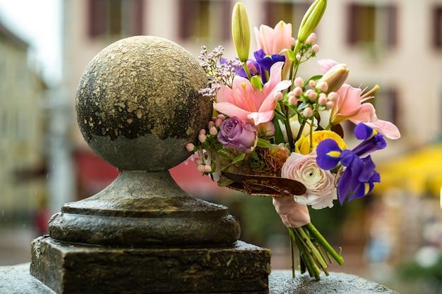 Ein hochzeitsstrauß mit lilien steht bei regenwetter auf der straße. hochzeitsdeko.