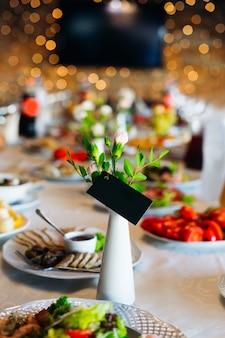 Ein hochzeitstisch mit vielen köstlichen gerichten und einer blumenvase mit einer visitenkarte
