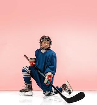 Ein hockeyspieler in uniform mit ausrüstung über rosa studiohintergrund. das athlet, kind, sport, aktionskonzept Premium Fotos