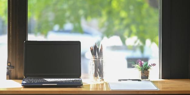 Ein hölzerner arbeitsbereich ist von einem computer-laptop, einer vase mit stiften, einer topfpflanze und einer zwischenablage umgeben.