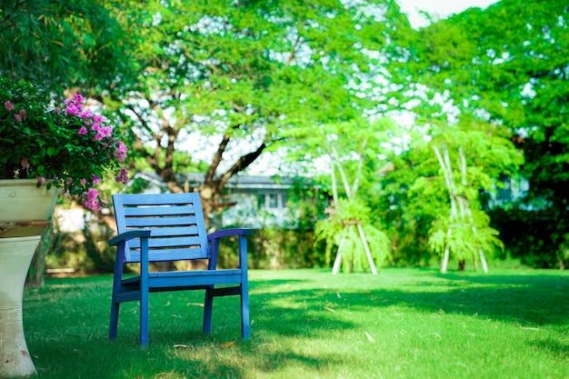 Ein hölzerner blauer stuhl allein im garten. fühlen sie sich einsam, aber entspannend und ruhestand