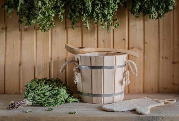 Ein hölzerner eimer und ein birkenbesen in einem russischen bad. sauna.