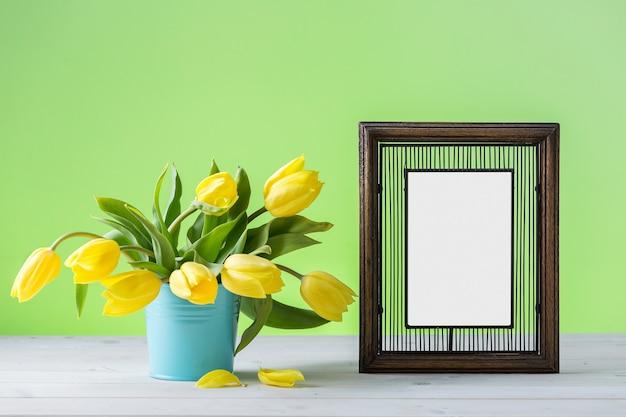 Ein hölzerner fotorahmen nahe gelben tulpen auf einer hölzernen oberfläche