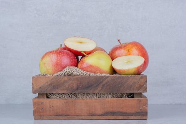 Ein hölzerner korb voller äpfel auf weißem hintergrund. foto in hoher qualität