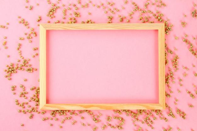 Ein hölzerner leerer rahmen auf einem pastellhintergrund umgeben durch glänzende dekorative sterne und bälle.
