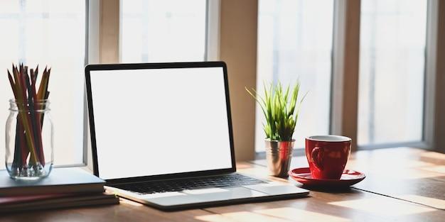Ein hölzerner schreibtisch ist von einem computer-laptop und zubehör umgeben