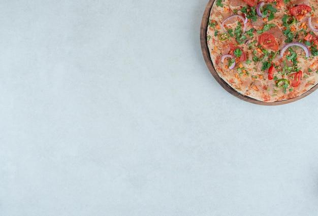 Ein hölzerner teller fladenbrot mit geschnittenen tomaten und zwiebeln.