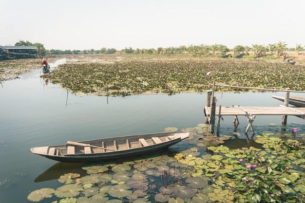 Ein hölzernes boot im schönen morgenlotosfeld auf dem see in einer provinz nahe bangkok, thailand.