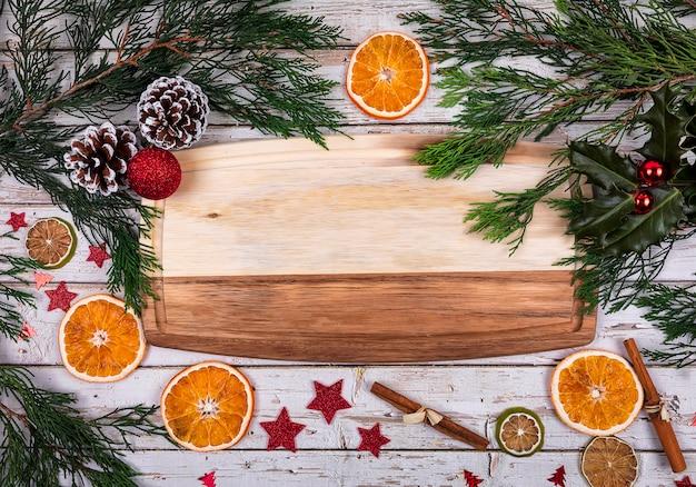 Ein hölzernes brett mit kopienraum für text im weihnachtsdekor mit weihnachtsbaum, trockener orange und kegel auf hintergrund