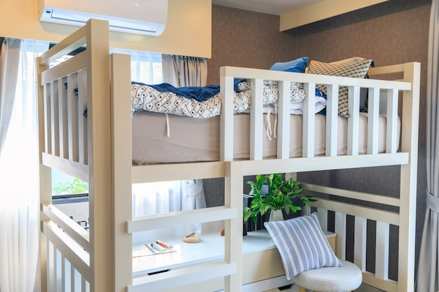 Ein hölzernes etagenbett mit einem kissen und einer klimaanlage in einem kinderzimmer.