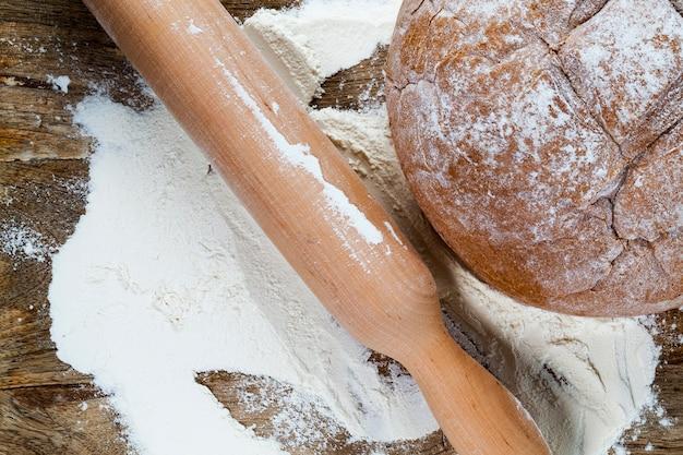 Ein hölzernes nudelholz in mehl und ein laib brot beim kochen