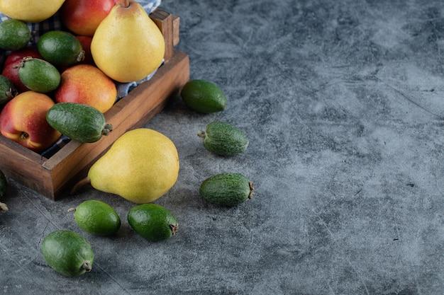 Ein hölzernes obsttablett voller birnen, feijoas und pfirsiche