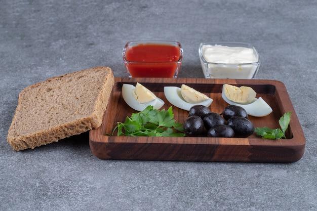 Ein hölzernes schneidebrett mit gekochtem ei und brotscheiben. hochwertiges foto