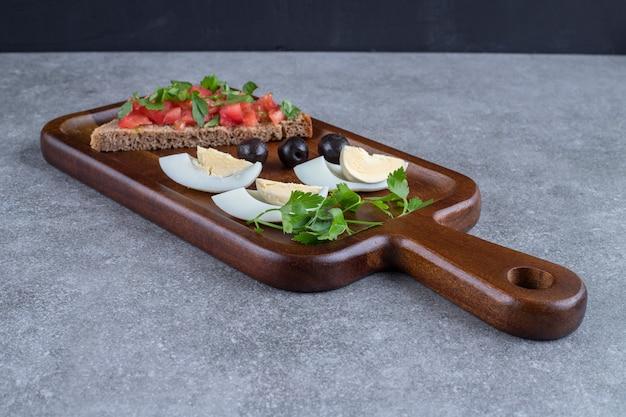 Ein hölzernes schneidebrett mit gekochtem ei und toast. hochwertiges foto