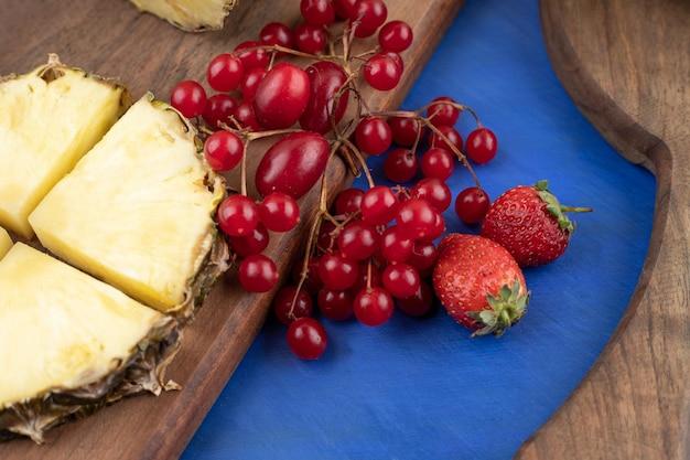 Ein hölzernes schneidebrett mit geschnittener ananas und roter johannisbeere