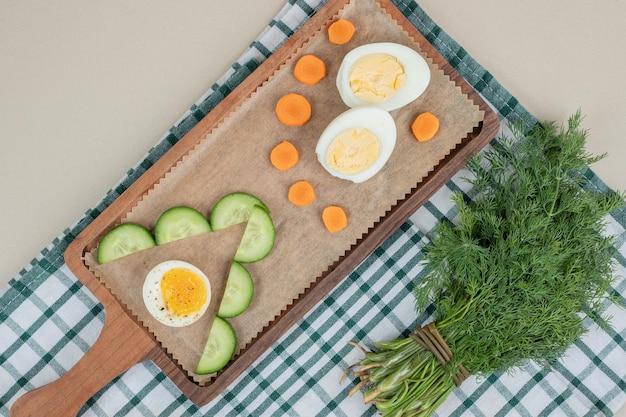 Ein hölzernes schneidebrett mit geschnittener gurke und gekochtem ei.