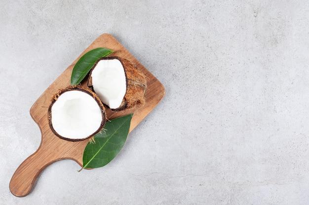 Ein hölzernes schneidebrett mit geschnittener kokosnuss und blättern. hochwertiges foto