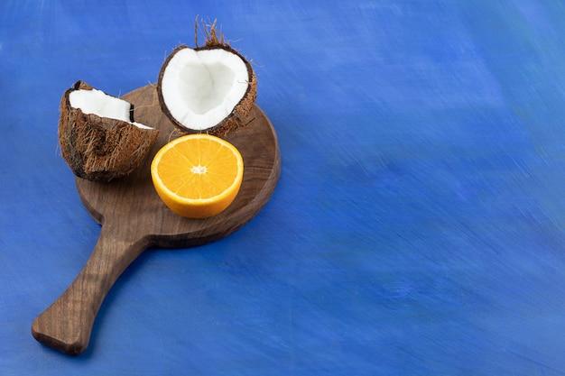 Ein hölzernes schneidebrett mit geschnittener kokosnuss und orange