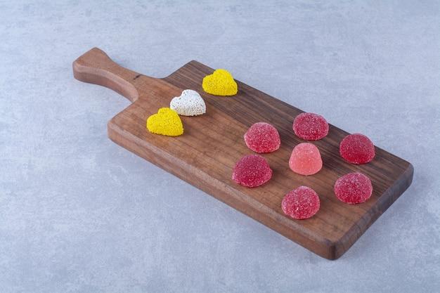 Ein hölzernes schneidebrett voller bunter zuckerhaltiger geleebonbons. foto in hoher qualität