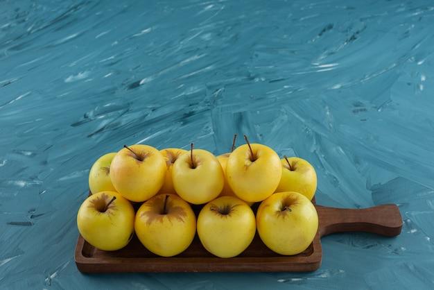 Ein hölzernes schneidebrett voller gelber apfelfrüchte.