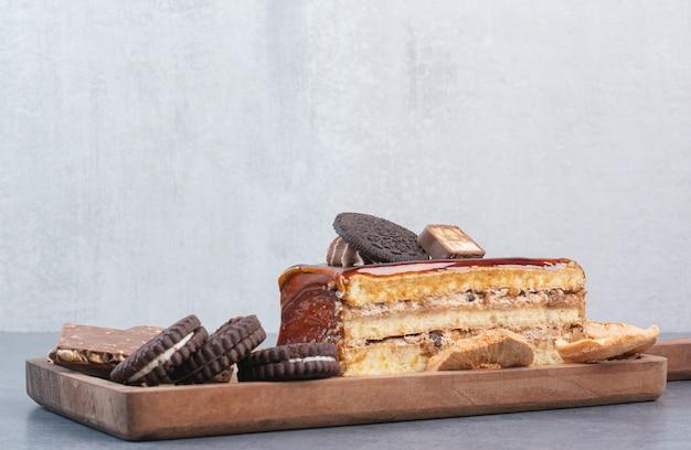 Ein hölzernes schneidebrett von keksen und ein stück kuchen.