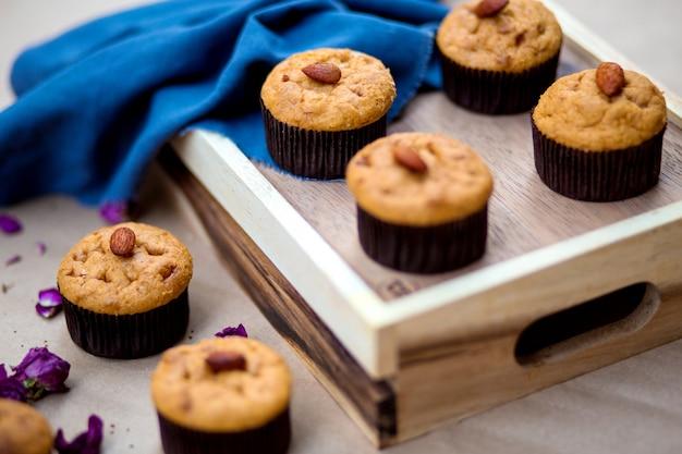 Ein hölzernes tablett mit einfachen muffins mit mandeln an der spitze