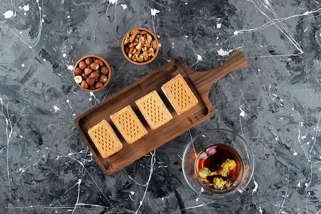 Ein holzbrett aus belqischen waffeln mit einer tasse tee und gesunden nüssen