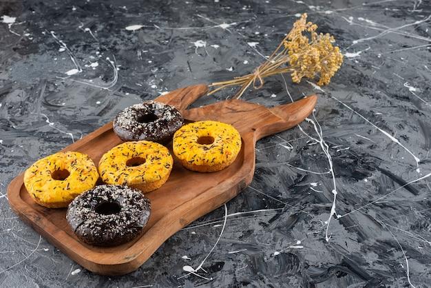 Ein holzbrett aus frischen donuts mit gelber und schokoladenglasierter glasur.