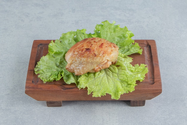 Ein holzbrett aus gebratenem hühnerfleisch mit salat.